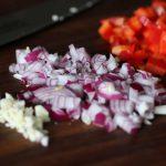 Zwiebeln, Knoblauch und Paprika - kleingehakt für die Metaxasauce