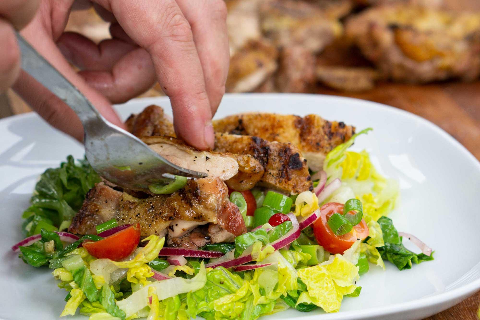 Gegrillte Hähnchen Steaks werden in Tranchen geschnitten und auf dem Salat platziert.