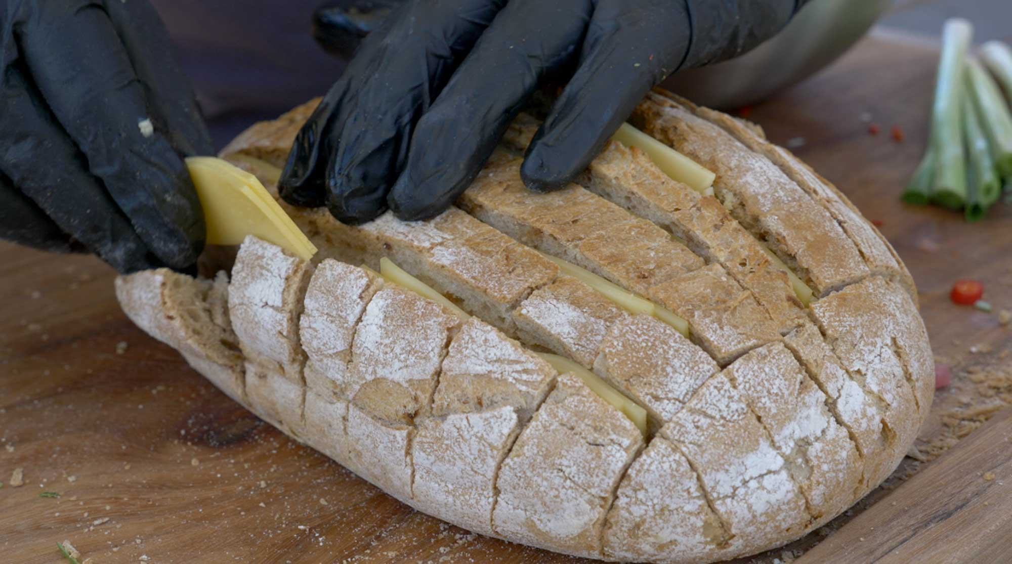 Der Käse wird in die Lücken des Zupfbrotes gesteckt