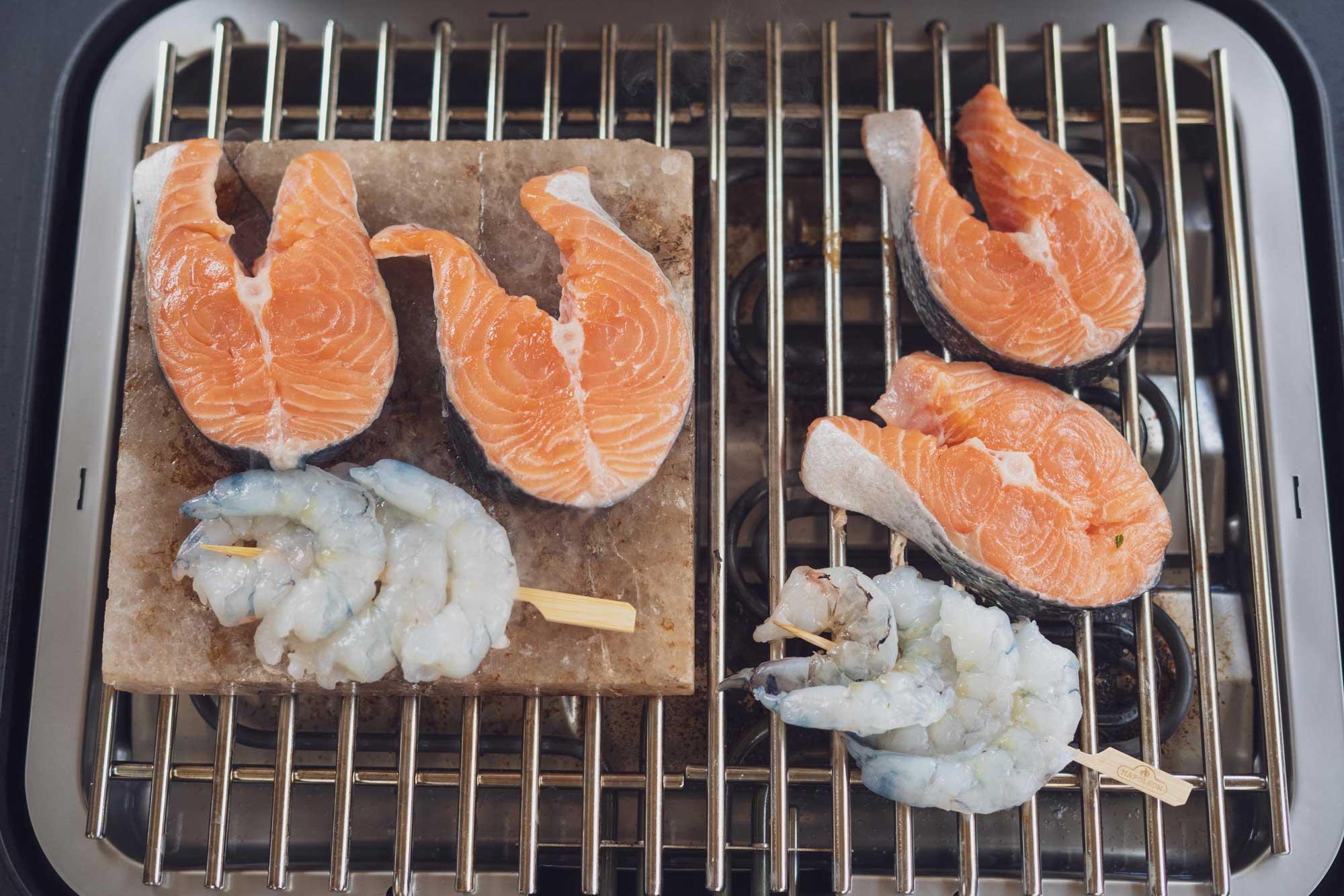 Lachs und Garnelen liegen auf dem Grill bzw. den Salzstein