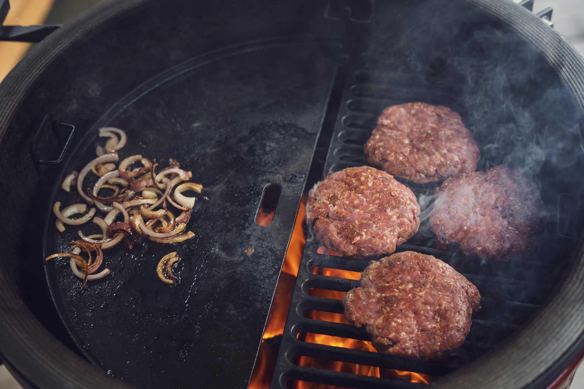 Im Baconfett werden die Zwiebeln gegrillt, während die Patties von dem Flammen geküsst werden
